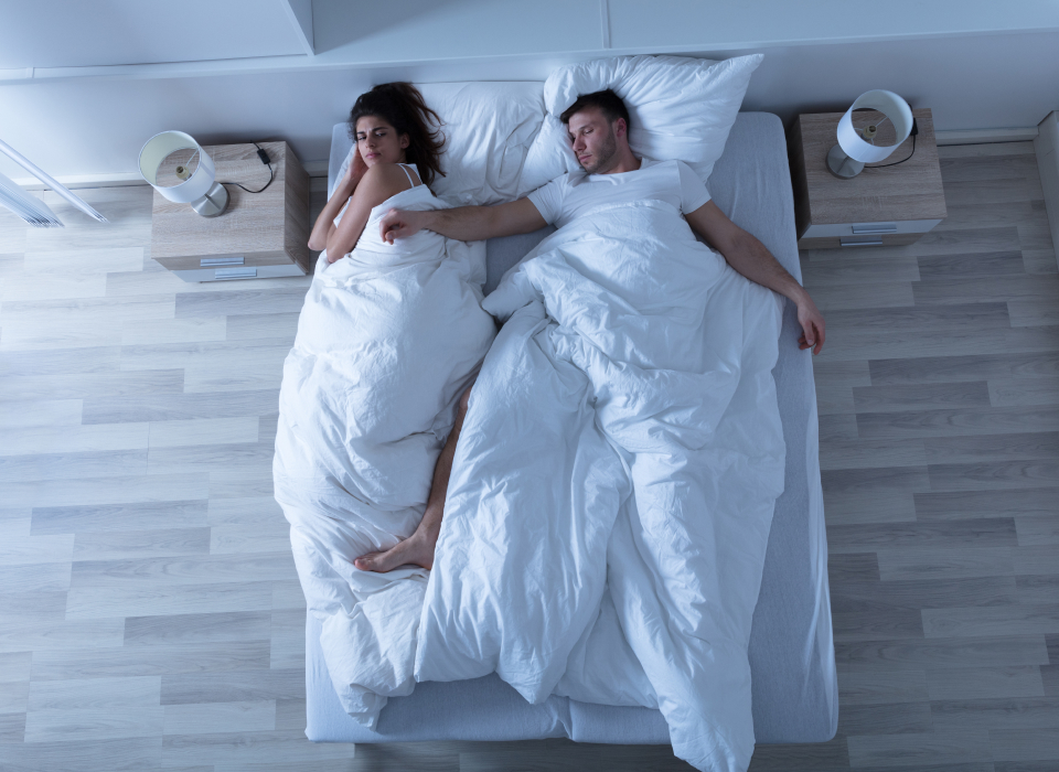 couple sleeping and man is spread across bed and woman is irritated
