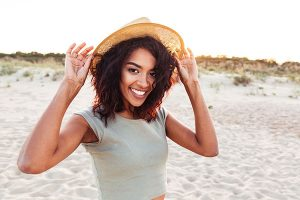 Young woman earing a sun hat and smiling on the beach