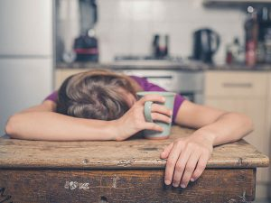 A woman sleeping facedown on a table with her hand around a coffee mug